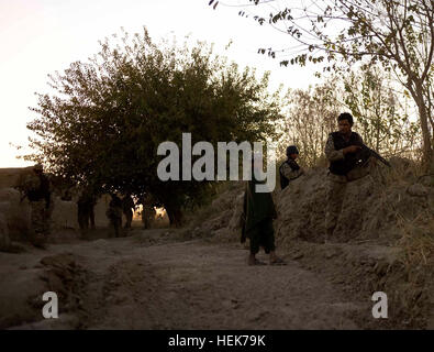 Policemen with 2nd Battalion, 3rd Afghan National Civil Order Police Brigade, speak with an Afghan boy during a - Stock Photo