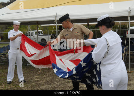 Sailors unfold an American flag in preparation for the raising of the colors at Cuzco Wells Cemetery at U.S. Naval - Stock Photo