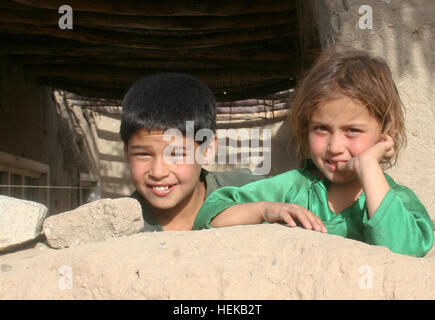 Two Afghan children watch from behind the wall of a khalat as U.S. Army soldiers from Company C, 1st Battalion, - Stock Photo