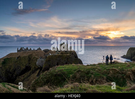 Photographers capturing the sunrise this morning at Dunnottar Castle, near Aberdeen in Scotland. - Stock Photo