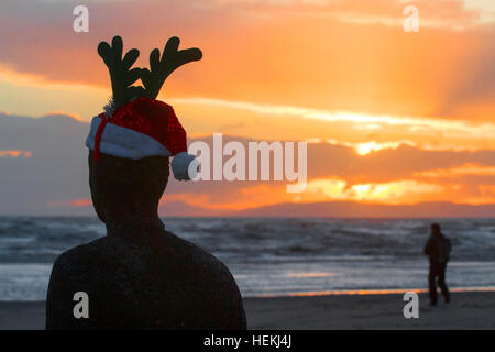 Sunset over Crosby, Liverpool, UK. 22nd Dec 2016. Weather.  A man walking on the beach at sunset, passes 'Antony - Stock Photo