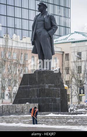 Donetsk, Donetsk Oblast, Ukraine. 20th Dec, 2016. Man cleans snow in the street under a huge statue of Lenin in - Stock Photo