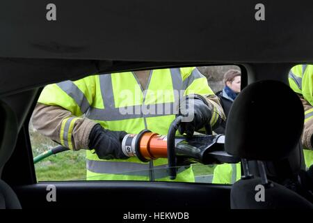 Firefighter cutting the roof off a car at the scene of an accident demonstration, UK. 'Car crash' scene, RTA or - Stock Photo