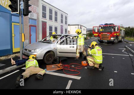 Firefighters working at the scene of an accident demonstration, UK. 'Car crash' scene, RTA or RTC, Crashed car with - Stock Photo