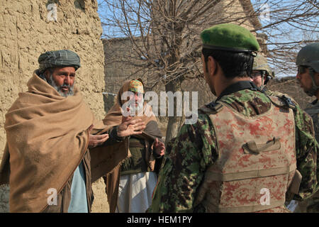 Local Afghan men speak with U.S. Army Staff Sgt. Jonathan Enlow, from Tahlequah, Okla., serving with Outlaw Platoon, - Stock Photo
