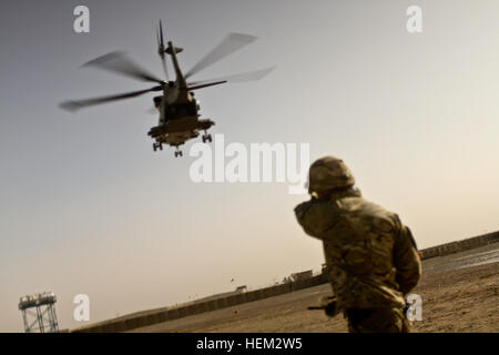 A British army soldier with the 1st Battalion, The Princes of Wales Royal Regiment, and a helicopter landing zone - Stock Photo