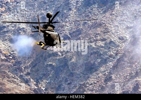An OH-58D Kiowa Warrior from Task Force Saber, 82nd Combat Aviation Brigade, fires a 2.75-inch rocket at a mountainside - Stock Photo