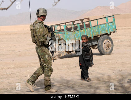 A soldier with coalition special operations forces greets an Afghan child during a security patrol in the Maiwand - Stock Photo