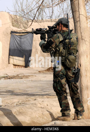 A soldier with the Afghan National Army special forces provides security while members of coalition special operations - Stock Photo