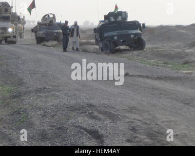 A convoy of American Soldiers, Afghan Soldiers and Afghan National Police (ANP) halt after discovering an IED buried - Stock Photo
