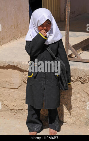 A young Afghan girl stands outside the Aliabad School near Mazar-e-Sharif, Balkh province, Afghanistan, April 3, - Stock Photo