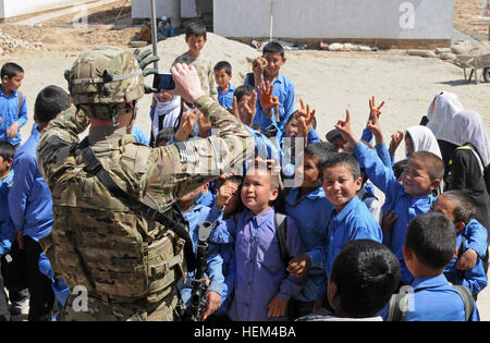 Afghan children wave for the camera of Spc. Aaron Burnside, analyst assigned to Bravo Company, Special Troops Battalion, - Stock Photo