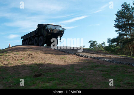 Soldiers drive a Heavy Expanded Mobility Tactical Truck, or HEMTT, during a run-through of an obstacle on the new - Stock Photo