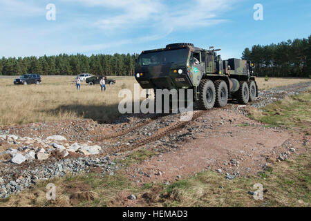 Soldiers gradually navigate a  Heavy Expanded Mobility Tactical Truck, better known as a HEMTT, through an obstacle - Stock Photo