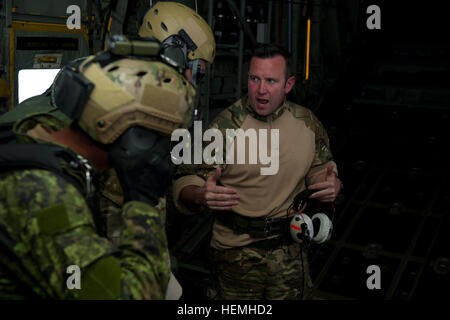 A Royal Air Force (RAF) jump master briefs jump masters from the Canadian Special Operations Regiment about wind - Stock Photo
