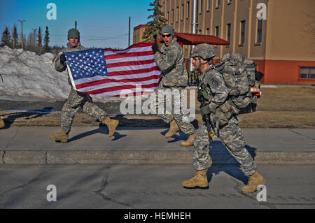 A U.S. Soldier with the 4th Brigade Combat Team, 25th Infantry Division, is cheered on by Soldiers as he moves to - Stock Photo