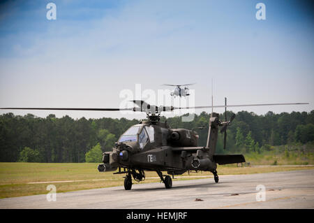 A U.S. Army AH-64D Apache helicopter taxis into the parking area at Ech Stagefield, Fort Rucker, Ala., May 22, 2013, as a second aircraft completes a final approach during the 'bag' portion of the Apache helicopter course, when a student's cockpit windows are completely covered. The goal is to force student pilots to fly the aircraft solely by reference to the AH64 Helmet Mounted Display, also known as Integrated Helmet and Display Sighting System (IHADSS).  The IHADSS provides a monocular display of outside the aircraft via television or thermal sensor on the nose of the aircraft.  (U.S. Army Stock Photo