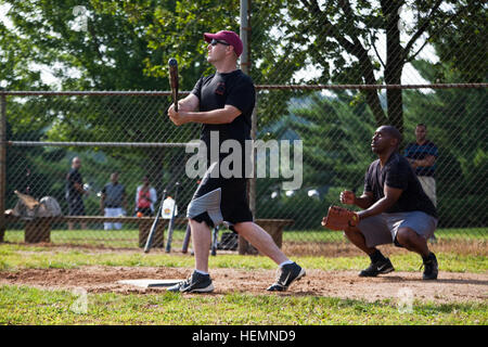 U.S. Army Sgt. Brian Kramer, 55th Signal Company (Combat Camera), hits a softball during a game held in Watkins - Stock Photo