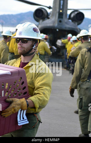 Zach Freundlich, with the San Juan Interagency Hotshots crew based in Durango, Colo., helps unload animals and evacuees - Stock Photo
