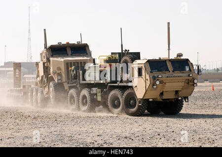 A Heavy Expanded Mobility Tactical Truck Wrecker tows a Heavy Equipment Transporter and trailer during a training - Stock Photo