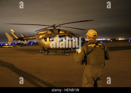 A Rio Grande Valley Border Patrol Agent stands in front of a Georgia Army National Guard LUH-72 Lakota before they - Stock Photo