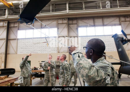 Pfc. Fanuel Chageza, foreground, tightens the cable on a Unit Maintenance Aerial Recovery Kit blade sleeve to stabilize - Stock Photo