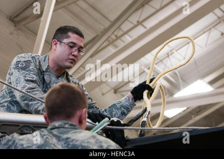 U.S. Air Force Tech. Sgt. Dax Rankin, of the 2nd Airlift Squadron, 43rd Airlift Wing, attaches cables in the Army's - Stock Photo