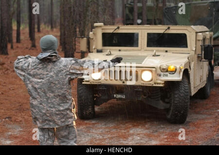 A soldier from the 362nd Quartermaster Battalion, 143rd Expeditionary Support Command, ground guides a Humvee into - Stock Photo