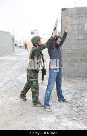 An Afghan National Security Force(ANSF) member searches a role player for incriminating evidence during tactical - Stock Photo