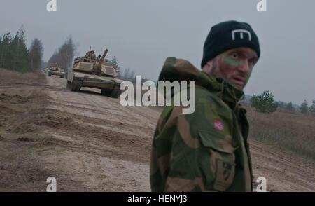 Norwegian sapper, Grenadier Jonricard Schau looks on as a U.S. Army M1A2 Abrams Tank moves past the defensive line - Stock Photo
