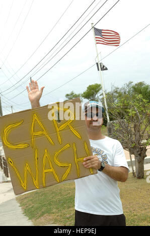 GUANTANAMO BAY, Cuba – Navy Chief Petty Officer Wesley Cole advertises on Sherman Avenue for the CPOA carwash fundraiser. - Stock Photo