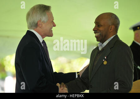 Secretary of the Navy Ray Mabus (left) congratulates Clinton Lee Suggs following an April 24 medal presentation - Stock Photo