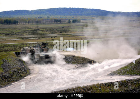 A M1A2 Abrams Main Battle Tank kicks up the dust after firing at a target as Soldiers from 2nd Battalion, 7th Infantry - Stock Photo