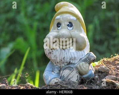 Garden gnome playing guitar. - Stock Photo