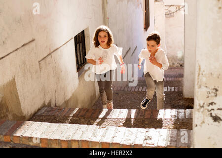 Boy and girl running up stairs, Granada, andalucia, Spain - Stock Photo