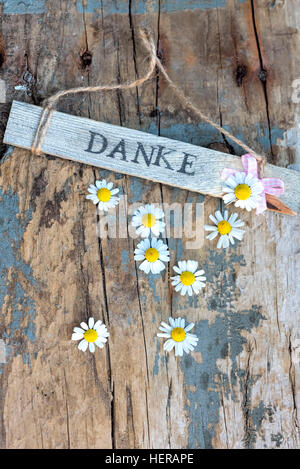 Sign with 'Danke' on old wooden board with small camomile blossoms - Stock Photo