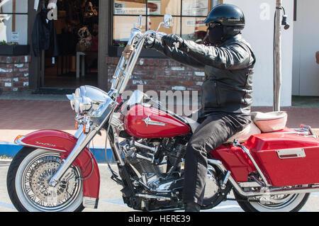 High level handle bars on motorbike in Danish Solvang  National Highway  1 Pacific Coast. Motorbiker on motorbike with black helmet reflection of