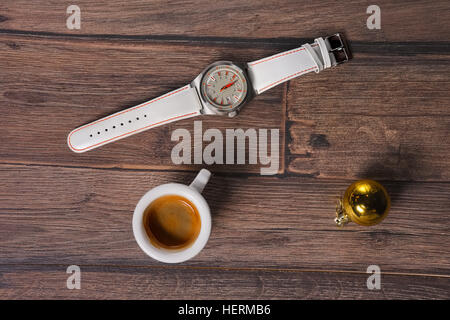 Top view of wrist watch, coffee and christmas tree toy on wooden table - Stock Photo