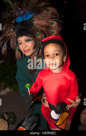 Mom wears outrageous peacock feathered hat daughter in Halloween Angry Bird costume trick or treating. St Paul Minnesota - Stock Photo