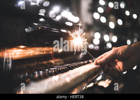 hand holding a sparkler over a piano - Stock Photo