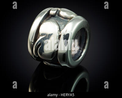 silver bead for on a bracelet on black - Stock Photo