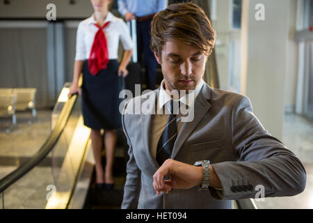 Businessman checking time while getting down the escalator at airport - Stock Photo