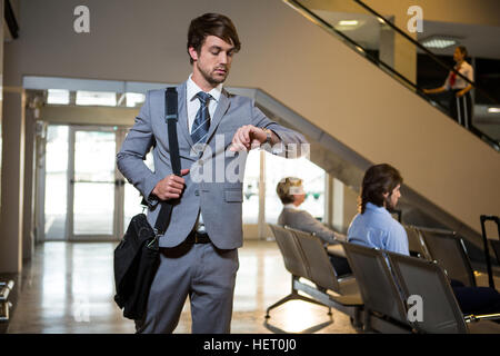 Businessman checking time while walking in waiting area at airport - Stock Photo