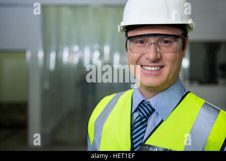 Technician in hard hat and protective eyewear at meat factory - Stock Photo