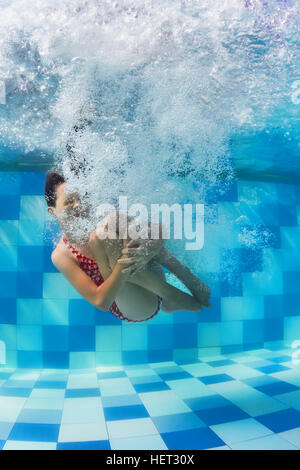 Funny face portrait of girl swimming and diving in blue pool with fun - jumping deep down underwater with splashes - Stock Photo