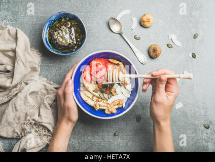 Blue bowl with healthy vegetarian breakfast ingredients in woman's hands - Stock Photo