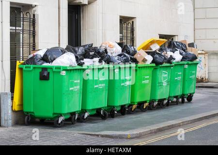 Overflowing commercial wheelie bin; rubbish bins on city centre street, Liverpool, UK - Stock Photo