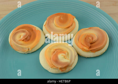 Pumpkin frosted sugar cookies on blue plate - Stock Photo