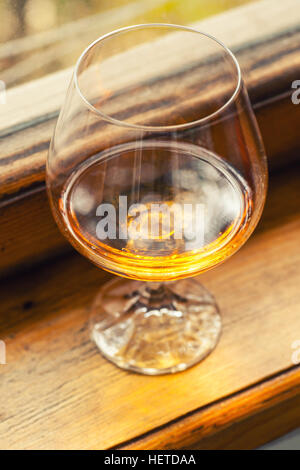 Brandy in a special snifter glass on a wood windowsill - Stock Photo
