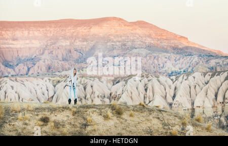 Young woman traveller hiking in mountains in Cappadocia, Central Turkey - Stock Photo